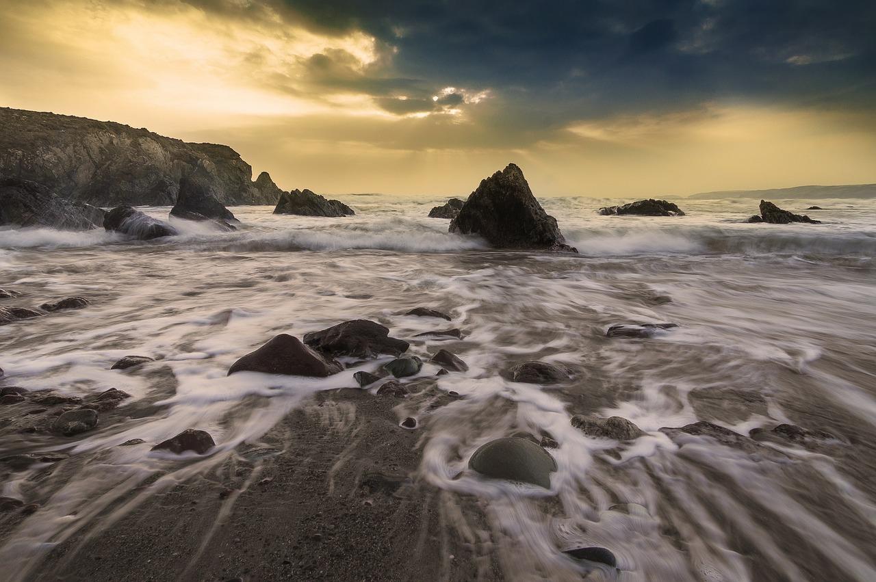 Meer trifft auf Strand und Felsen und schleift diese - Neptun trifft auf Saturn